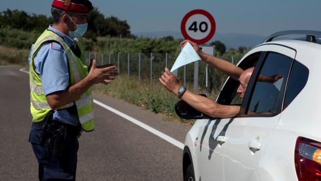 Un mosso da explicaciones a un conductor ilerdense tras decretarse el confinamiento del Segrià.