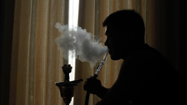 Una persona fumando cachimba.