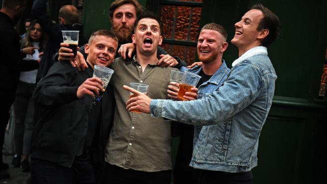 Varias personas bebiendo a las puertas de un pub en Londres.