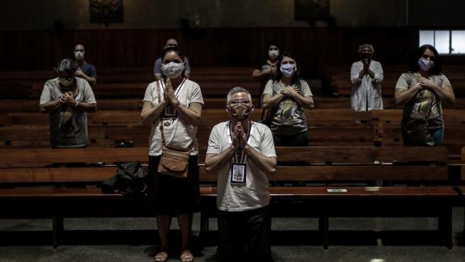 Varios fieles con mascarillas por el coronavirus, durante una misa en Río de Janeiro, Brasil.