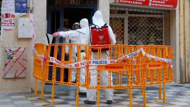 El personal sanitario desinfectando el edificio de Albacete donde ha habido un brote de Covid-19.