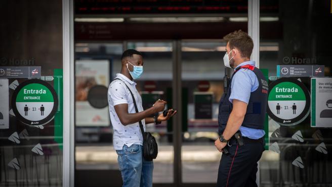 Un Mosso d'Esquadra habla con un hombre en la entrada de la Estación de Tren de Lleida.