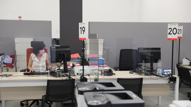 Una trabajadora de la Oficina del Empleador protegida con mascarilla y con una pantalla separadora en su mesa