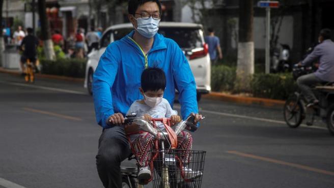 Un hombre y un niño con mascarillas por el coronavirus circulan en bicicleta por una calle de Pekín, China.