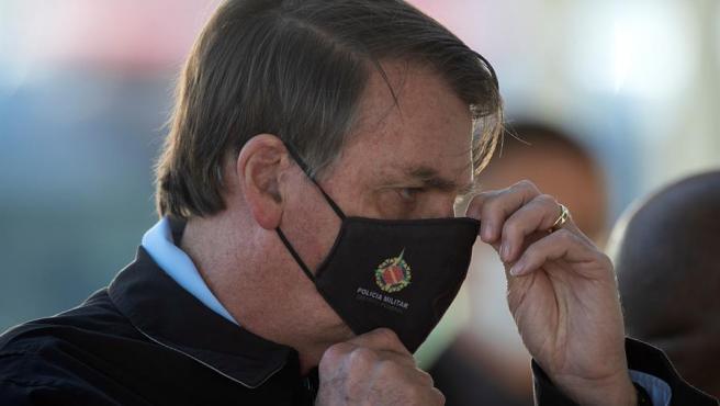 El presidente de Brasil, Jair Bolsonaro, se acomoda una mascarilla con el logotipo de la Policía Militar, en Brasilia.