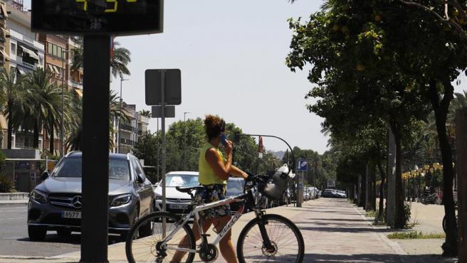 Una mujer pasa debajo de un termómetro digital en el centro de Córdoba.