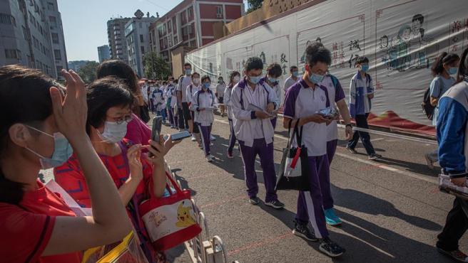 Estudiantes con mascarillas por el coronavirus desfilan en Pekín, China, para hacer el examen nacional de acceso a la universidad, conocido como Gaokao.