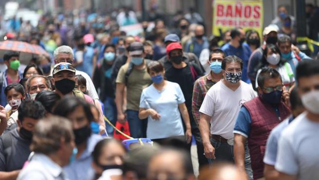 Docenas de personas hacen fila para entrar en el centro histórico de Ciudad de México, a traves de 'filtros sanitarios' instalados para reducir los contagios de COVID-19.