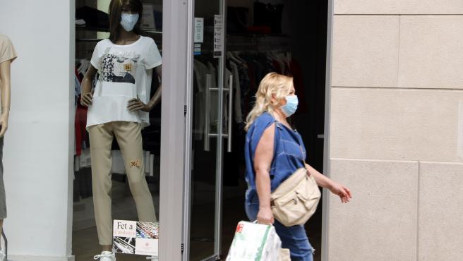 Una mujer camina con mascarilla y bolsas de la compra, delante de un escaparate donde el maniquí también lleva, en Mollerussa (Lleida).