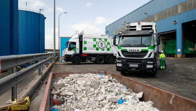 Un contenedor con escombros juntoa dos camiones de basura del Ayuntamiento de Madrid, a las puertas del Parque Tecnológico de Valdemingómez.