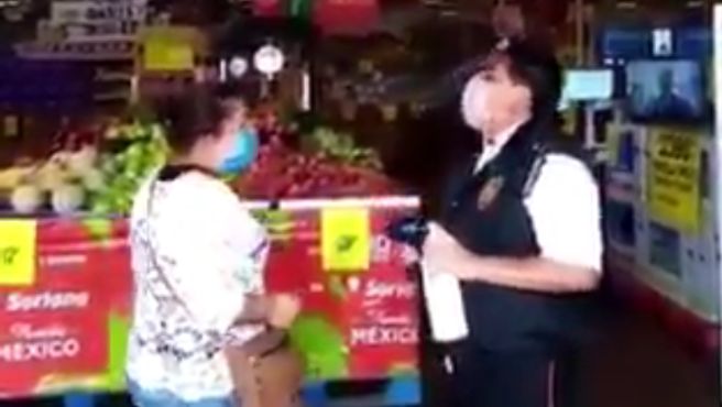 Un guardia tomando la temperatura a una clienta de un supermercado.
