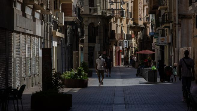 Varias personas caminan por una calle del centro de Lleida, capital de la comarca del Segrià, en Lleida, Catalunya (España), a 6 de julio de 2020. El presidente de la Generalitat, Quim Torra, anunció el pasado sábado el confinamiento perimetral por 14 día