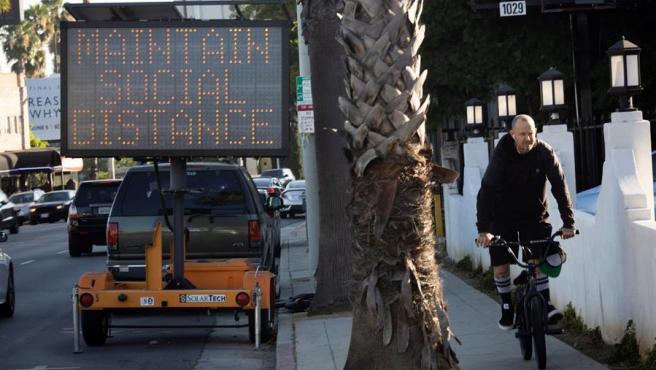 Un letrero West Hollywood, California (EE UU), recuerda la necesidad de mantener distancia física por la pandemia del coronavirus.