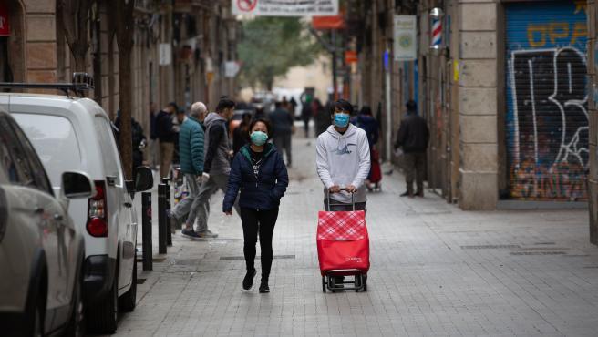 Dos personas protegidas con mascarillas durante el segundo día laborable del estado de alarma por el coronavirus, en Barcelona (España), a 17 de marzo de 2020.