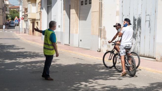 Un agente cívico informa a unos jóvenes de la obligación del uso de la mascarillla en Alcarràs (Lleida).