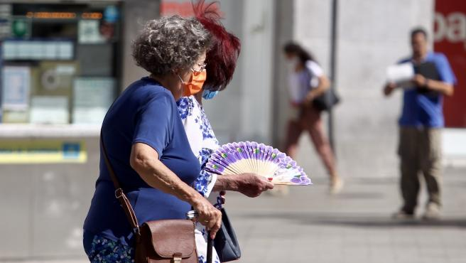Dos personas abanicándose por la calle a causa del calor.