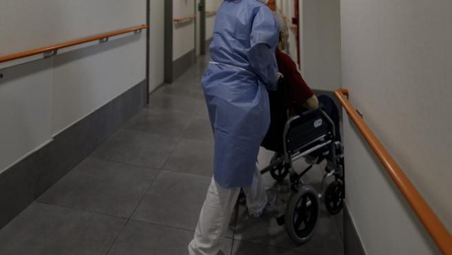 Una técnico sociosanitario del Centro de Mayores Casablanca Villaverde (Av. de Rafaela Ybarra, 135) lleva a un residente a su habitación cuatro días después de que se decretase el fin del estado de alarma por el COVID-19.