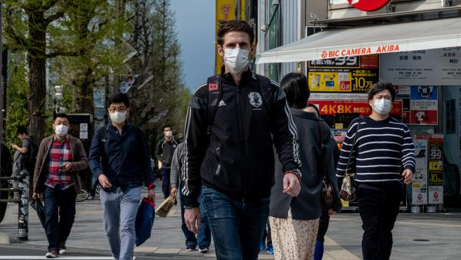 Varias personas con mascarilla caminan en Tokio (Japón).