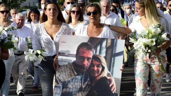 La esposa del conductor de autobús francés Philippe Monguillot, Veronique Monguillot (C), flanqueada por dos de sus hijas, sostiene un retrato de su esposo durante una marcha en Bayona.