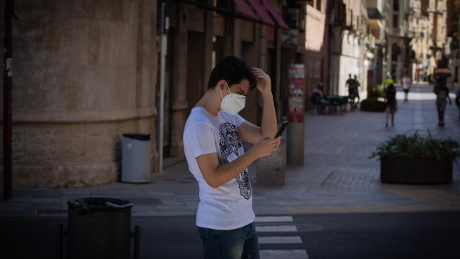 Un joven con mascarilla camina mirando el móvil.