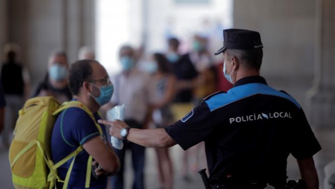 Más de 6.800 agentes de Policía Nacional, Local y Guardia Civil forman el dispositivo de la jornada electoral en Galicia. En la imagen, varias personas aguardan en la fila para votar en un colegio electoral de A Coruña.