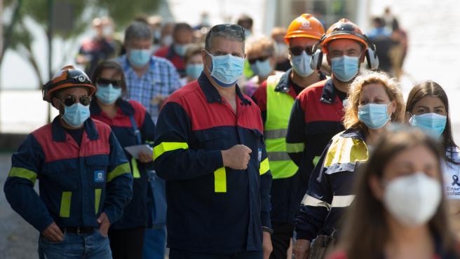 Trabajadores de Alcoa acuden a votar ataviados con los uniformes.