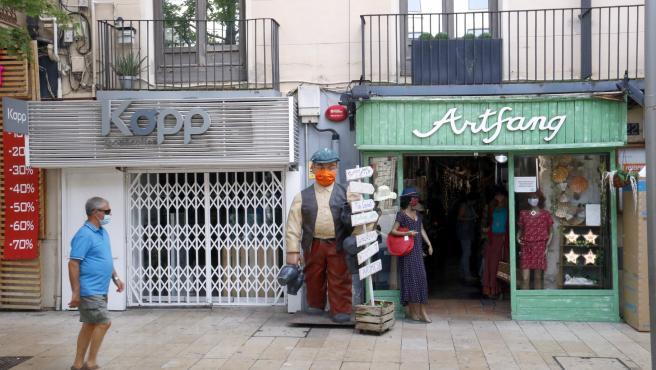 Un bar cerrado al lado de una tienda abierta en el Eje Comercial de Lleida.