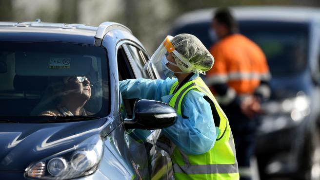 Una sanitaria realiza una prueba rápida en un coche en Australia.