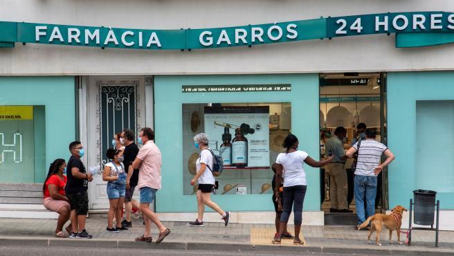 Varias personas hacen cola en una farmacia 24 horas de Lleida