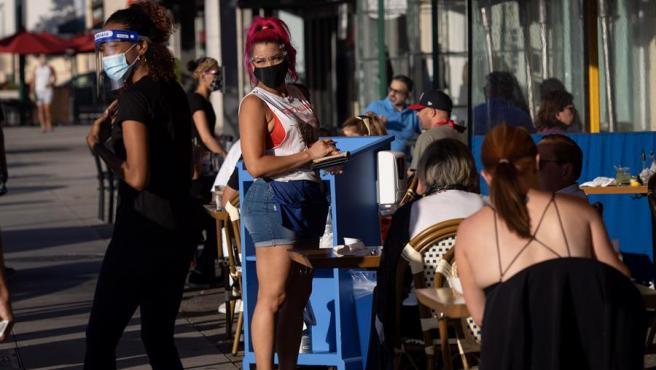 Una camarera con mascarilla por el coronavirus, en la terraza de un restaurante en West Hollywood, California (EE UU).