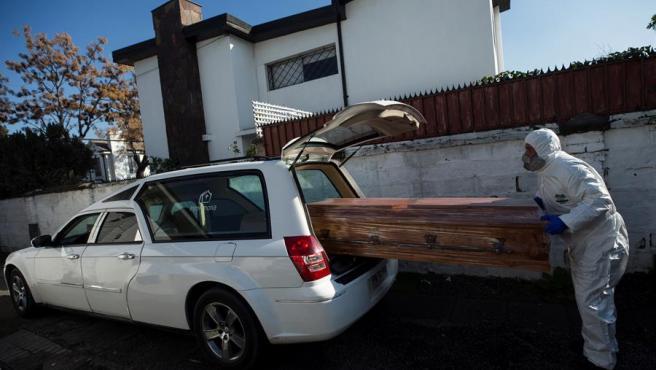 Un trabajador de una funeraria carga un ataúd a un coche fúnebre antes de ir a recoger a un fallecido por COVID-19, en Santiago (Chile).