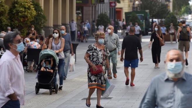 Varias personas con mascarilla caminan por las calles de Huesca.