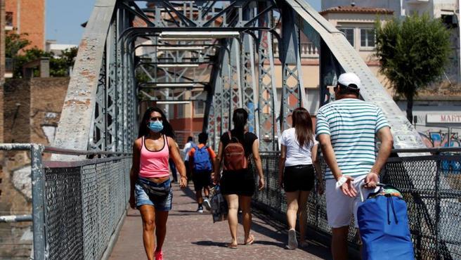 Varias personas con mascarillas por el coronavirus cruzan el puente de la Torrassa, en L'Hospitalet de Llobregat, Barcelona.