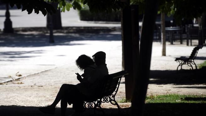 Una pareja sentada en un banco en el Parque del Retiro en Madrid (España), a 29 de junio de 2020. El calor pone desde este lunes en aviso a una quincena de provincias de Andalucía, Castilla y León, Castilla-La Mancha, Extremadura y Madrid, por temperatura
