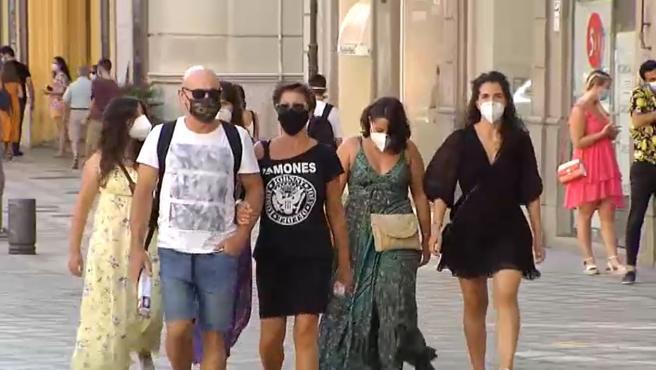 Varias personas con mascarilla pasean por la calle.