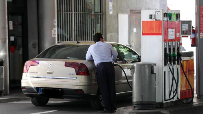 Personas ponen gasolina en sus coches en una gasolinera de Madrid.