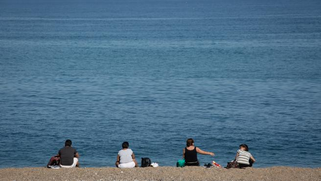 Varias personas sentadas en la Playa de la Barceloneta respetan la distancia de seguridad.