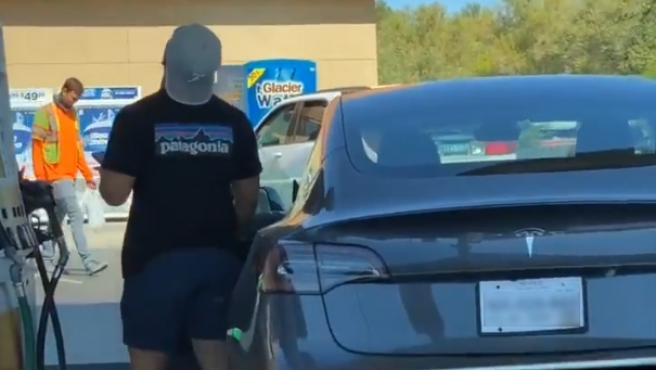 El joven, intentando encontrar el depósito de combustible de su coche eléctrico