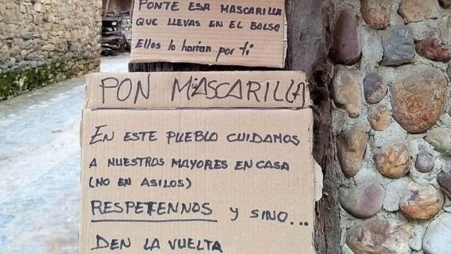 Cartel en la entrada de un pueblo de Asturias dirigido a los visitantes que van sin mascarilla.