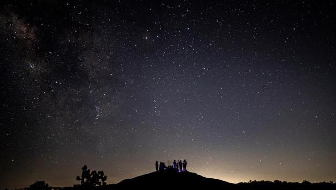 Una familia observa el cometa tras la puesta de sol en el parque nacional de Joshua Tree, California.