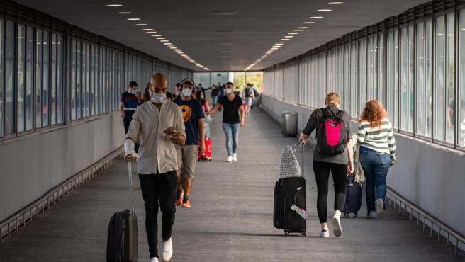 Varios pasajeros en uno de los pasillos de la T2 del Aeropuerto de El Prat (Barcelona).