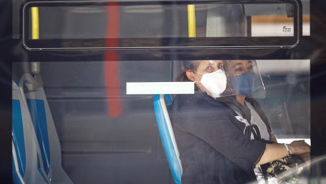 Dos mujeres con mascarilla y pantalla se sientan al lado en un autobús de la EMT en Madrid.