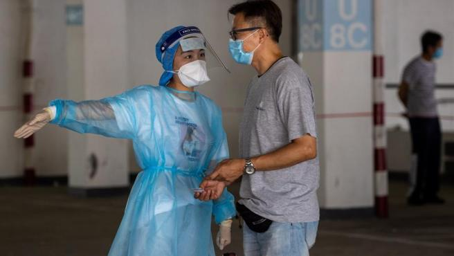 Una trabajadora sanitaria atiende a un taxista en un aparcamiento convertido en centro de test de coronavirus en Hong Kong, China.