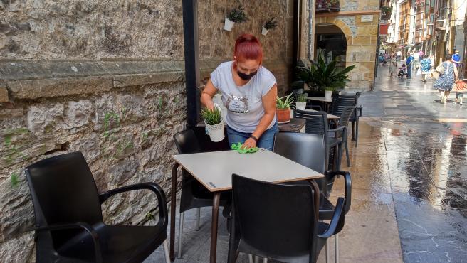 Una trabajadora desinfecta la mesa de la terraza de uno de los locales hosteleros