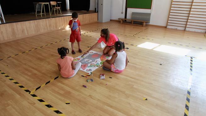 Dos grupos de niños participan en una actividad durante el campamento de verano