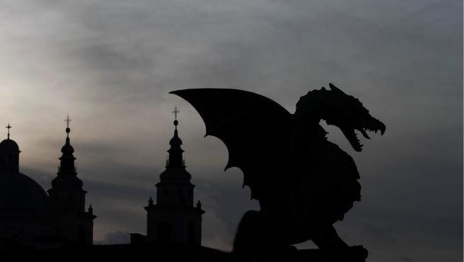 La silueta de un dragón se alza junto a unas torres.