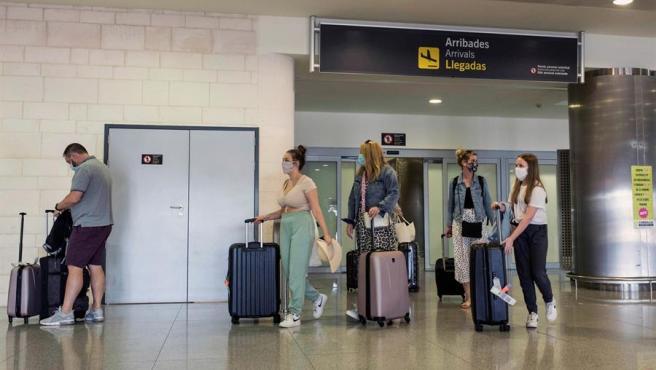 Varios turistas con mascarillas por el coronavirus llegan al aeropuerto de Menorca en un vuelo procedente de Londres.