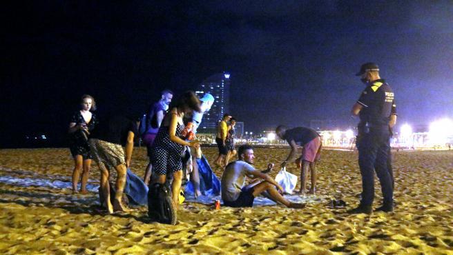 Un grupo de personas que hacía botellón en la playa de la Barceloneta se levantan ante la presencia de agentes de la Guardia Urbana.