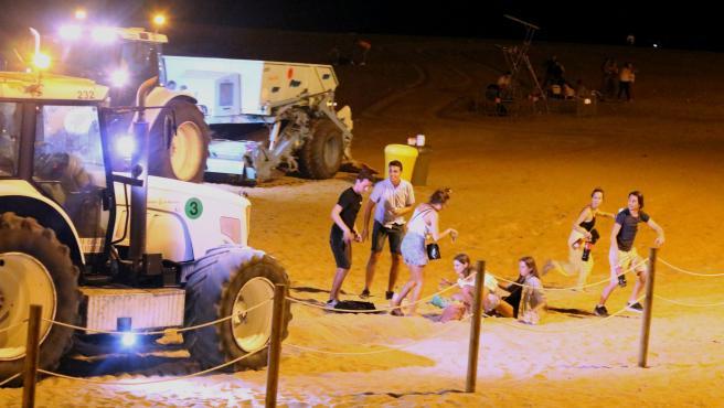 Un grupo de jóvenes que hacía botellón en la playa de la Barceloneta se levantan por la llegada de un tractor de la limpieza, poco antes de la una de la madrugada.