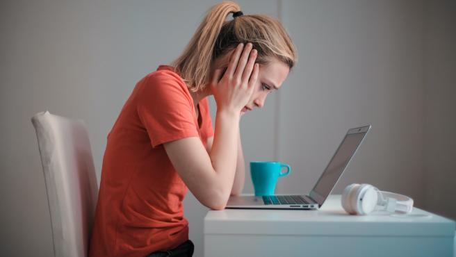 Una mujer, triste y preocupada ante su ordenador portátil